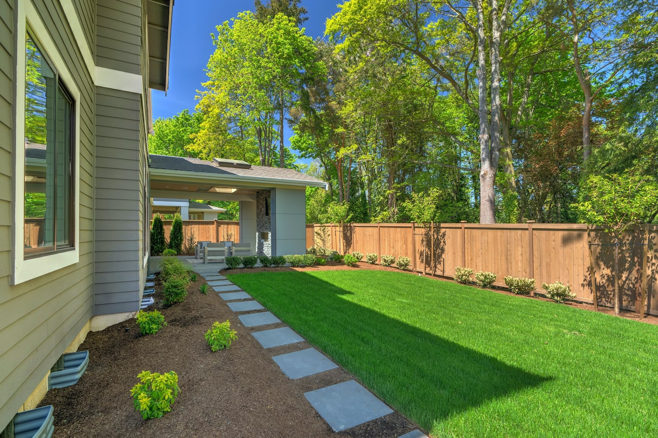 Residential landscaping with green grass and wood fence